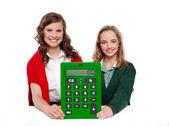 Chicas mostrando gran verde calculadora para cámara — Foto de Stock