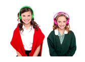 Schoolgirls listening music through headphones — Stock Photo