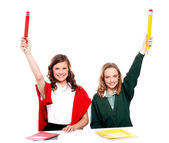 Students showing big pencil in raised arm — Stock Photo