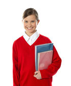 Cheerful schoolgirl holding books — Stock Photo