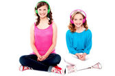 Teenage friends sitting on floor listening music — Stock Photo