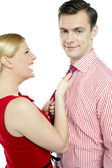 Glamorous woman pulling man by his tie — Stock Photo