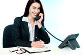 Operator receiving call on telephone and writing — Stock Photo