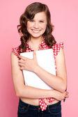 Joyful teenage girl holding spiral notebook — Stock Photo