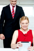 Boss operating tablet pc and assistant looking — Stock Photo