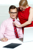 Female adjusting her co-workers tie — Stock Photo