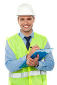 Construction engineer writing on notepad — Stock Photo