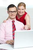 Corporate couple enjoying videos on laptop — Stock Photo