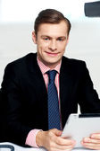 Young executive posing with tablet pc — Stock Photo