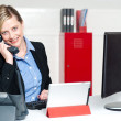 Smiling female secretary attending phone call — Stock Photo