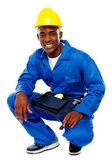 Seated african worker posing with a smile — Stock Photo