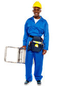 African repairman holding stepladder — Stock Photo