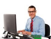 Happy young corporate man using computer — Stock Photo