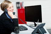 Female secretary answering bosses call — Stock Photo