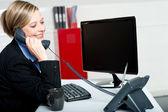 Female secretary answering bosses call — Stock Photo