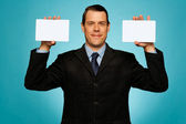 Businessman showing two blank white placards — Stock Photo
