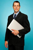Businessperson carrying a laptop — Stock Photo