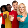 Smiling group of with thumbs up gesture — Stock Photo