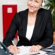 Smiling woman wearing headset writing on notepad — Stock Photo #12130817