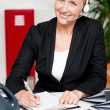 Smiling woman wearing headset writing on notepad — Stock Photo