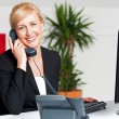 Secretary talking on phone with client — Stock Photo