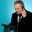 Stock Photo: Irritated businessmcommunicating on phone
