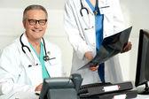 Frau assistentin vorlage röntgen-berichts auf männlichen arzt — Stockfoto