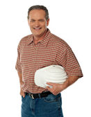 Smiling senior architect holding white safety hat — Stock Photo