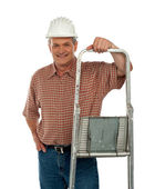 Smiling aged worker posing with ladder — Stock Photo