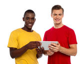 Technology savvy friends using tablet pc — Stok fotoğraf