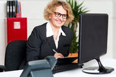 Its time to work. Front desk lady making notes — Stock Photo