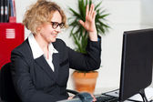 Smiling woman with raised arm looking at screen — Stock Photo