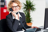 Front desk lady attending clients call — Stock Photo