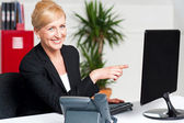 Businesswoman pointing at computer screen — Stock Photo