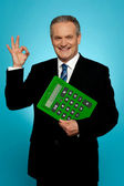 Confident executive holding calculator and gesturing okay sign — Stock Photo