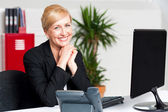 Aged businesswoman sitting with hands on chin — Stock Photo