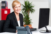 Smiling corporate woman typing on keyboard — Stock Photo