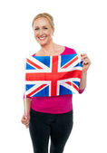 Cheerful female supporter holding national flag — Stock Photo
