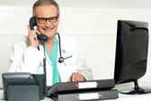 岁医生出席在液晶屏幕前调用液晶画面の前にコールに出席医者高齢者 — ストック写真