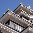 Roof a traditional Japanese castle against blue sky - Stock Photo