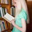 Female university student reads a book in the library — Stock Photo