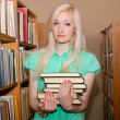 Royalty-Free Stock Photo: Female university student holding books in library