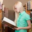 Royalty-Free Stock Photo: Female university student reads a book in the library