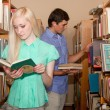 Young woman and man in the library looking for a book — Stock Photo