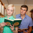 Young woman and man in the library reading book — Stock Photo #11525410