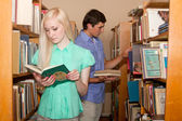 Молодая женщина и мужчина в библиотеке, глядя на книгу — Стоковое фото