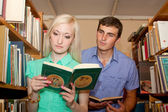 Young woman and man in the library reading book — Stock Photo