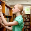 Young girl in the library looking for a book — Stock Photo #11539998
