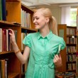 Stock Photo: Young girl in the library looking for a book