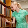 Young girl in the library looking for a book — Stock Photo #11540042